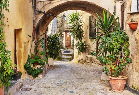 Narrow street with flowers in the old town Coaraze in France