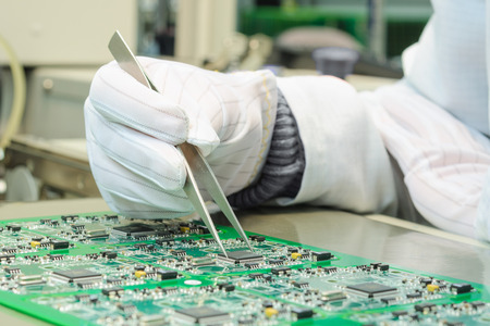 Quality control and assembly of SMT printed components on circuit board in QC lab of PCB manufacturing high-tech factory
