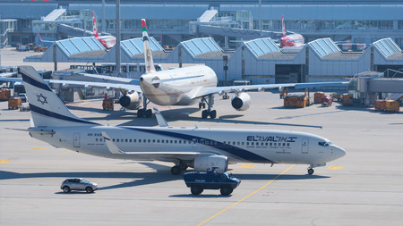 Munich, Germany - May 6, 2016: Aircraft Boeing 737-800 by Israeli airline El Al taxiing to airport terminal with escort armored vehicle ensures antiterrorism force protection