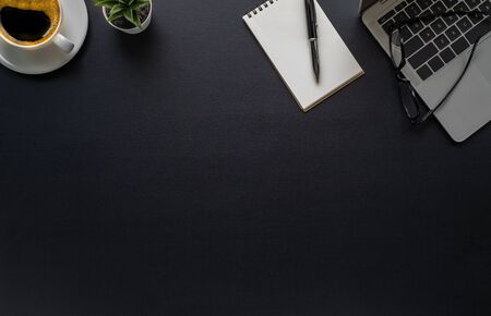 Photo for Workspace in office with black table. Top view from above of laptop with notepad and coffee. Desk for modern creative work of designer. Flat lay with blank copy space. Business and finance concept. - Royalty Free Image