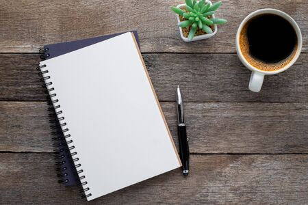 Photo for Top view from above of Blank open notebook and coffee on wood table background. Workplace for the creative work of designer at home. Flat lay, Business-finance or education concept with copy space. - Royalty Free Image