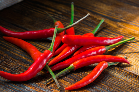 Pile of Mexican mini chili peppers on wooden background. Burning seasoning
