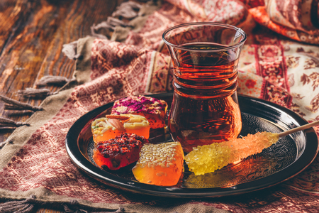 Photo for Tea in armudu glass with oriental delight rahat lokum on metal tray over wooden surface and tablecloth - Royalty Free Image
