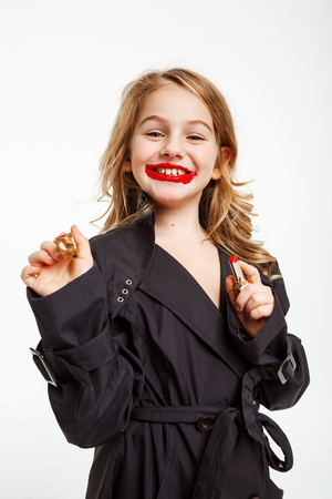 Cute little girl in coat copying mother, putting on red lipstick, smiling cheerfuly, looking straight.