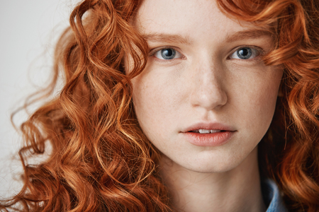 Photo for Close up of beautiful natural ginger girl with freckles looking at camera. White background. - Royalty Free Image