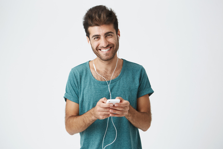 Studio shot of looking happy young man broadly smiling as he talks to his girlfriend during online call using earphones and his electronic gadget. People, technology and communication concept