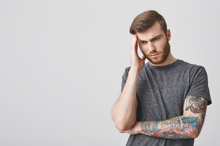 Good-looking tattooed mature sad man with beard and fashionable hairstyle massaging forehead with hand, looking aside painful expression, being exhausted with strong headache.