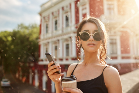 Photo pour Summer days. Close up portrait of attractive skinny feminine caucasian woman with dark hair in tan-glasses and black dress, waiting for boyfriend that being late for date, chatting with friend by smartphone, drinking coffee, looking in camera with calm expression. - image libre de droit