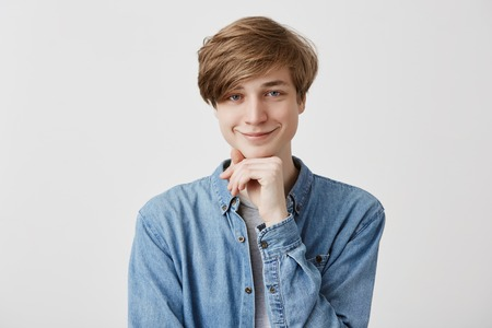 Happiness, positiveness and people concept. Smiling pleased fair-haired young man in denim shirt, keeps hand under chin, rejoices coming weekends, has grandious plans to spend time with friends