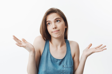 Photo pour I dont know, sorry. Attractive funny dark-haired caucasian girl in casual clothes looking aside with awkward expression, spreading hands. Woman pretending she dont know anythting about others man t-shirt in house. - image libre de droit