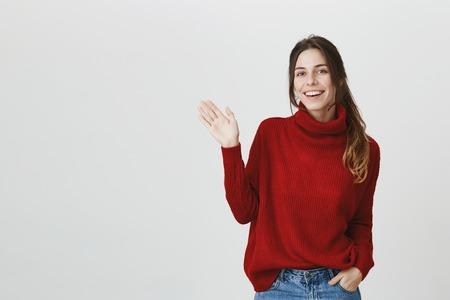 Young attractive student with beautiful long brown hair smiling broadly, waving showing hello gesture over white background. Pleasant attractive girl came to her work, greeting coworkers cheerfully.