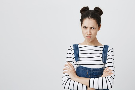 Picture of funny brunette girl in denim overall posing at studio, keeping arms folded, having offended look, pouting lips, showing her dislike, negative attitude and reaction.