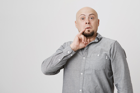 Studio shot of bald bearded man in gray shirt poses against gray background, holds little finger behind corner of his mouth, looks like Dr. Evil. Hairless male grimacing and making faces indoors
