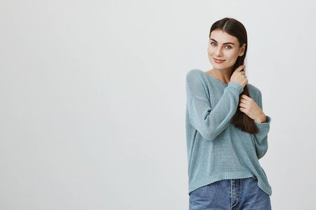 Waist-up portrait of Caucasian beautiful attractive young female model with long dark hair dressed in casual clothes posing indoors, pleased to hear compliments, touching her hair.