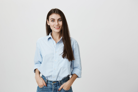 Photo pour Beautiful and successful young woman smiling confidently with hands in pockets, looking at camera while standing over gray background. Dance teacher greets her new group of students - image libre de droit