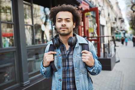 Outdoor portrait of stylish dark-skinned traveler with afro hairstyle walking on street. Man tries to find hostel where he booked a room to stay during journey to foreign country