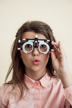 Horizontal shot of excited cute european brunette checking vision with phoropter, being interested in how it works, waiting for optometrist to prescribe appropriate glasses