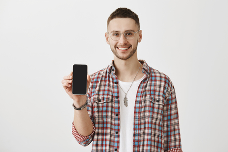 Photo pour Convenient and functional smartphone. Portrait of handsome bearded model showing cellphone at camera and smiling broadly while advertising it over gray background. Gadget that can help stay in touch - image libre de droit