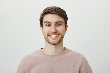 Confident attractive caucasian guy in beige pullover smiling broadly while standing against gray background, feeling self-assured while helping out customer, giving some advice about his investments