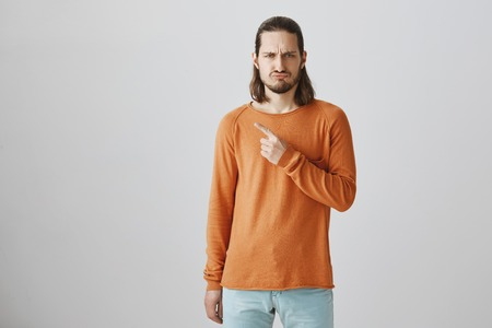 Portrait of good-looking offended guy in orange sweater pointing at upper left corner, sulking and frowning, being jealous or disappointed