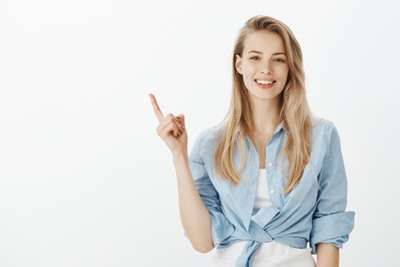 Photo pour Indoor shot of creative stylish blond woman with broad smile, raising index finger while pointing at upper left corner, having great idea or suggestion, indicating at perfect spot for copy space - image libre de droit