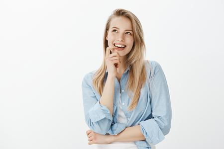 Photo for Creative good-looking female designer with blond hair, biting finger, looking up and smiling curiously while having great idea, standing dreamy over gray background, having interesting plan - Royalty Free Image