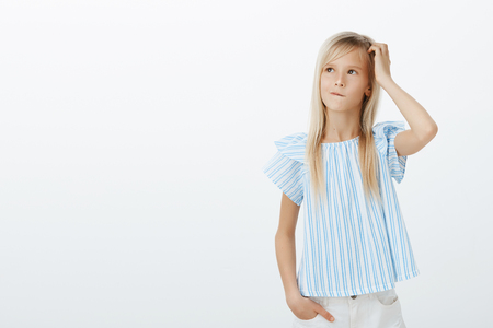Photo pour Kind adorable girl making idea how to cheer up mom. Confused concerned little child with fair hair, scratching head and looking up while thinking or planning next step, clueless and unaware - image libre de droit