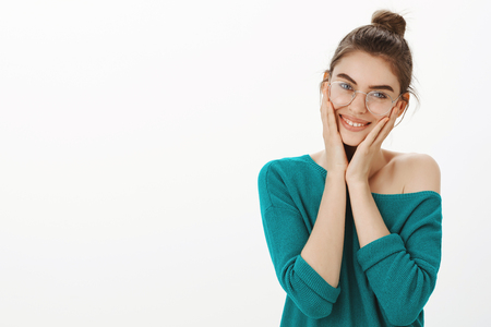 I am so happy to have such loving friends. Portrait of emotional pleased and tender female in loose sweater and glasses, holding palms on cheeks and smiling with cute expression, being touched