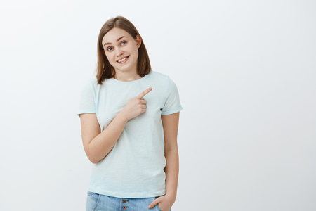 Studio shot of shy cute carefree brunette sportswoman in trendy t-shirt stooping tilting head and smiling friendly and proud pointing at upper right corner showing her medals posing over white wall