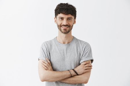 Waist-up shot of confident good-looking mature european male entrepreneur in t-shirt holding hands crossed in self-assured pose and smiling with assured pleasant smile over gray background