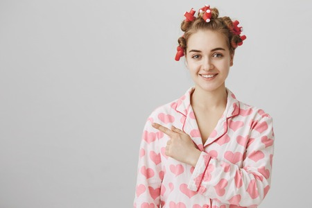 Good-looking funny caucasian female in hair-curlers smiling charmingly and pointing left or behind, standing over gray background in pajamas. Girl shows boyfriend where he can find towel