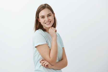 Waist-up shot of friendly-looking joyful lucky girl with brown short haircut standing in profile holding hand on cheek and turning at camera with broad happy smile posing against grey wall