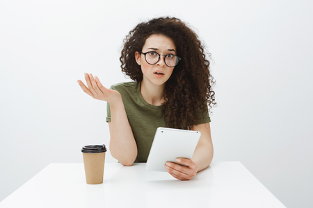 Studio shot of clueless confused charming woman with curly hair in eyewear, raising hand in questioned gesture, sitting at table, drinking coffee and holding white digital tablet over gray background