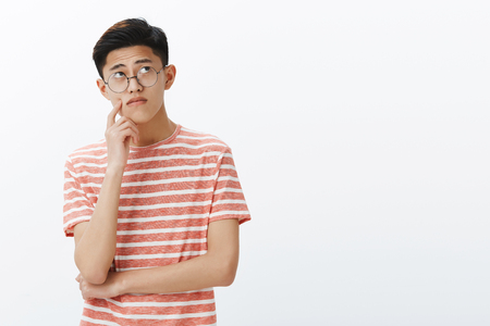 Photo pour Smart asian guy solving puzzle in mind looking thoughtful and relaxed at upper right corner, thinking, making assumptions touching cheek while making up plan or decision, posing in glasses - image libre de droit