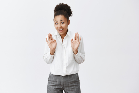 Photo pour Worried and nervous cute dark-skinned female coworker in suit, waving palms near chest in no, take it easy or deny gesture, smiling from anxiety over gray background - image libre de droit
