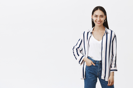 Foto de Indoor shot of creative good-looking stylish designer in striped blouse and stylish jeans, holding hand in pocket while smiling broadly at camera, standing in relaxed and confident pose over gray wall - Imagen libre de derechos