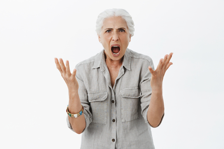 Foto per Portrait of dissatisfied furious and angry grandmother with white hair in casual shirt raising palms in clueless gesture shaking hands and yelling frowning feeling anger and fury while arguing - Immagine Royalty Free