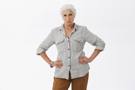 Photo pour Explain you behavior young man. Portrait of strict and disappointed mad granny standing in displeased pose with hands in waist frowning staring angry at camera being dissatisfied posing over gray wall - image libre de droit