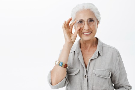 Waist-up shot of charming kind and nice granny in sight glasses touching rim of eyewear and smiling joyfully helping grandson prepare for exams posing joyful and delighted over grey wall