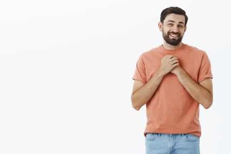 Guy touched with cute gift holding palms near heart smiling delighted and happy receiving surprising gift smiling joyfully at camera tilting head posing in pink t-shirt against gray background
