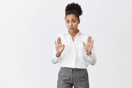 Photo pour Take it easy, calm down friend. Worried cute african-american female in white shirt and pants, pulling palms towards camera in no or stop gesture, cheering person who is drunk over gray background - image libre de droit