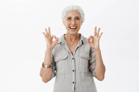 Photo for I recommend this place. Portrait of delighted and satisfied cute granny with grey hair in casual shirt showing okay or excellent gesture and smiling broadly approving great idea over gray background - Royalty Free Image