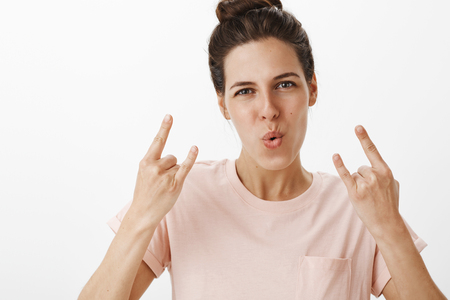 Foto de Girls rock this world. Portrait of energized and confident good-looking woman showing rock-n-roll gesture folding lips in cheer making self-assured expression as having fun at party over gray wall - Imagen libre de derechos