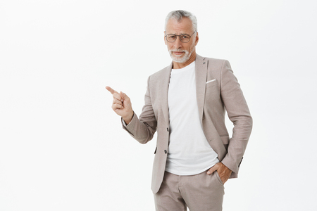 Portrait of arrogant and stylish good-looking old father in stylish formal suit and glasses holding hand in pocket pointing at upper left corner being doubtful and displeased underestimating someone