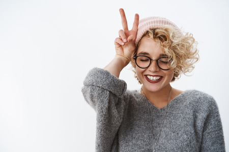 Photo pour Close-up shot of woman loving winter and holidays having fun feeling happy and tender close eyes joyful wearing beanie and sweater smiling broadly showing peace, victory sign near head - image libre de droit