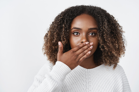 Photo for Indoor shot of surprised and stunned woman gasping from shock cover mouth speechless and amazed looking worried at camera reacting to shocking unexpected situation over white background - Royalty Free Image