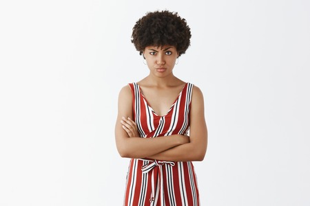 I am not trusting your words. Suspicious, doubtful beautiful African woman with afro hairstyle, raising one eyebrow, staring intense at camera, holding hands crossed, feeling doubtful and displeased