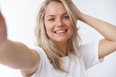Photo pour Woke up like this. Portrait of charming active and happy young blond woman feeling healthy taking vitamins, extend arm at camera taking selfie on smartphone posing with hand on haircut and smile - image libre de droit