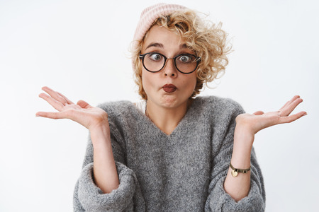 Photo pour Indoor shot of funny and playful immature woman fooling around sticking out tongue squinting and looking at own nose spread hands sideways as aping from boredom over white background - image libre de droit