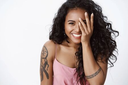 Photo pour Close-up cheerful happy african american girlfriend with tattoos and toothy white smile, laughing, cover half of face, gazing camera upbeat, enjoy party with friendly company, having fun - image libre de droit